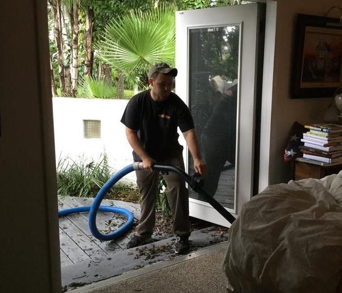 Technician extracting water from carpet through exterior door