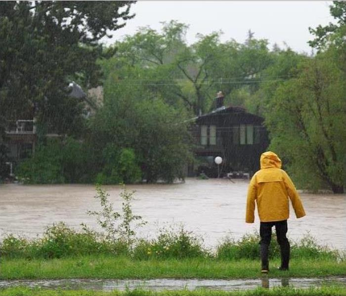 Person in a yellow raincoat standing by a river flooding nearby homes.